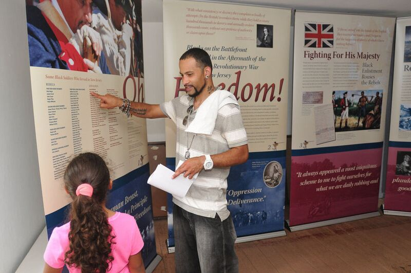 Aaron English of West Deptford, NJ points out the name of an African American solider during the Revolutionary War to his daughter Lea, 6, at the Oh Freedom! African Americans in the Revolution traveling exhibit at Red Bank Battlefield National Park, June 8, 2014. The exhibit, co-authored by NPS ranger Joe Becton, was developed by the New Jersey Office of Historic Sites. Photograph by Joe Warner; courtesy South Jersey Times.